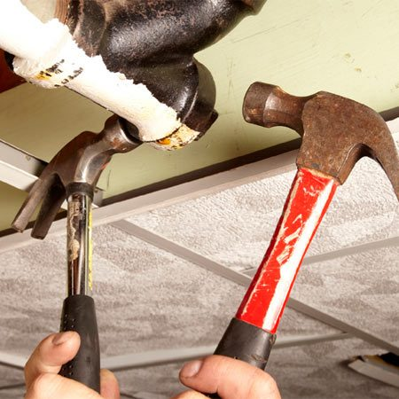 <b>Photo 2: Apply rust penetrant and vibration</b></br> <p>Soak the  cleanout plug threads with rust penetrant. Then   smack  opposite sides of the tee or wye   fitting <em>at  the same time </em>using two   hammers.  Rotate the double blows   around  the entire fitting. Then try using   a pipe  wrench again. </p>