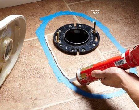 <b>Caulk the floor</b></br> Cut the caulk tube tip square and drag the caulk gun toward you as you lay in a thick bead of caulk along the inside edge of the tape.