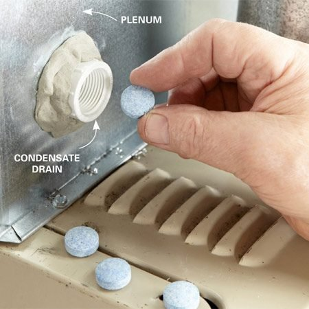 <b>Photo 1: Treat the pan with tablets</b></br> Shove the tablets into the drain pan opening and push them in farther using a dowel or long screwdriver. Add new tablets monthly during air-conditioning season, or less often if you rarely use your A/C.