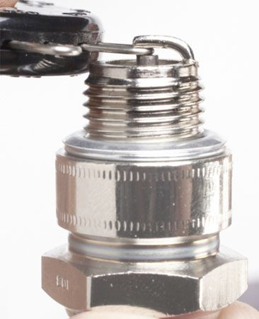 """<b>Photo 1: Check the gap with a gap gauge</b></br> Find the """"gapping wire"""" that matches the recommended gap. Then slide it between the center and side electrodes. When the gap is correct, the gauge should drag slightly going in and out. If the gap is too large or the wire won't fit, adjust the side electrode."""