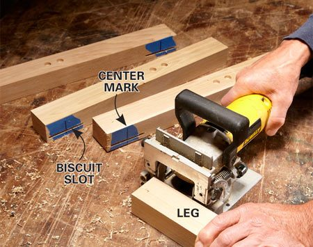 <b>Photo 2: Cut biscuit slots for the seat rails</b></br> <p>Mark the centers of the    biscuit slots on masking    tape. Then, with the plug    recesses facing up, cut the    slots in the narrow sides of    the legs. Keep the plate    joiner and leg tight to the    bench top as you cut. Use    tape to avoid marks on the    wood and to keep track of    the orientation of the pieces. </p>