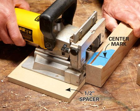 <b>Photo 3: Position slots for the long rails</b></br> Orient the leg so the previously cut slot is facing up, and cut a slot on the side opposite the plug holes. Use a spacer to position the slot so the long rail will be centered on the leg when it's installed.
