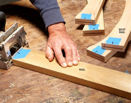<b>Photo 4: Cut slots in the rail ends</b></br> Mark the centers of the curved seat rails and long rails on masking tape. The tape also helps you keep track of the orientation of the slots.