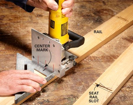 <b>Photo 5: Cut slots in the long rails</b></br> Position the long rails with the masking tape facing down. Use a Speed Square as a guide for cutting biscuit slots for the intermediate rails. Align the square with the edge mark for the seat rail. Make a center mark on the square as a reference for lining up the plate joiner.
