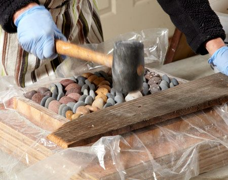 <b>Photo 4: Tamp the stones level to the tops</b><br/>Lay a board across the stones and pound on it with a rubber mallet to embed the stones in the dry mortar and set the tops level with each other.