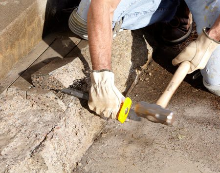 <b>Photo 3: Break out the blocks</b></br> Aim the chisel at the same depth as the saw cuts and whack away. The squares of concrete created by your saw cuts will pop off neatly (well, usually).