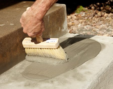 <b>Photo 7: Resurface the whole thing</b></br> Resurfacer hides the mismatch between old and new concrete and masks small imperfections. Pour it on and spread it with a masonry brush.