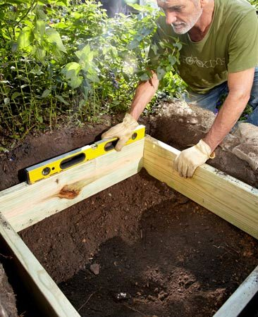 <b>Photo 1: Dig a hole and lay in a wooden frame</b><br/>Add or remove dirt from under the frame to level it. Remove rocks, dirt chunks and other debris from the dirt and rake it roughly level. Pour a 1/2- to 1-in. layer of sand over the dirt and level it out.