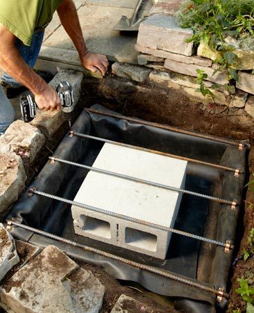 <b>Photo 2: Line the frame and add rebar</b><br/>Lay the pond liner in the frame and fold the corners. Set the two concrete blocks in the center. Attach lengths of rebar about every 8 in. Complete the reservoir by adding a layer of hardware cloth.