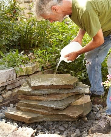 <b>Photo 3: Build the backyard waterfall</b></br> Spread a layer of gravel over the hardware cloth. Then start stacking the stone. Pour water over the stones occasionally to see how it's flowing.