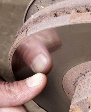 <b>Photo 2: Check the rotor's condition</b></br> Run your fingernail across the rotor surface. If your nail catches in deep grooves, the rotors should be machined or replaced as a pair.