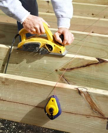 <b>Planning a deck joist</b></br> Stretch a chalk line across the joists to find high spots and plane them down.