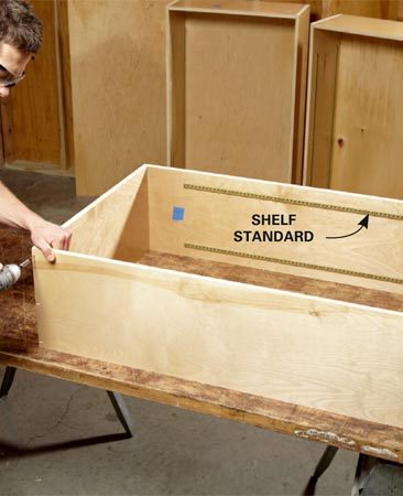 <b>Photo 4: Assemble the wall cabinets</b></br> Mount shelf standards on the cabinet sides before assembly. Then screw the sides to the bottom and top with 1-5/8-in. screws. Drill pilot holes to prevent the plywood from splitting.