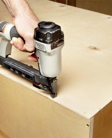 <b>Photo 5: Square the cabinet with the plywood back</b></br> Use the plywood back as a guide for squaring the cabinet. Apply a bead of glue. Then nail one edge of the plywood back to the cabinet side. Then adjust the cabinet box as needed to align the remaining edges and nail these.