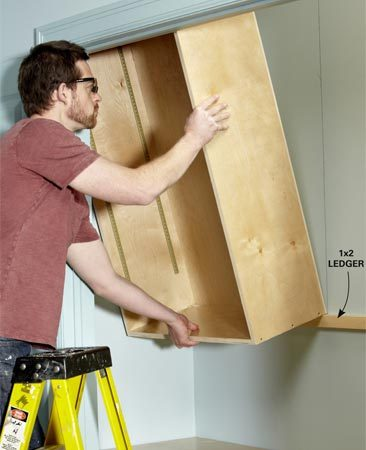 <b>Photo 6: Install the cabinets</b></br> Rest the bottom of the cabinet on the ledger and tilt the cabinet up. Drive 3-in. screws through the hanging strip at the top of the cabinet into the studs.