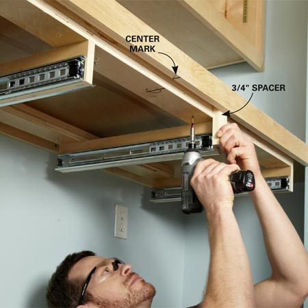 <b>Photo 10: Hang the frame under the countertop</b></br> Make center marks on the frame and the underside of the counter and align them. Then use a spacer to set the frame 3/4 in. back from the countertop edging and drive the screws.