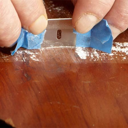 <b>Use a delicate paint scraper</b></br> Make a delicate paint scraper from a razor blade and two pieces of masking tape.