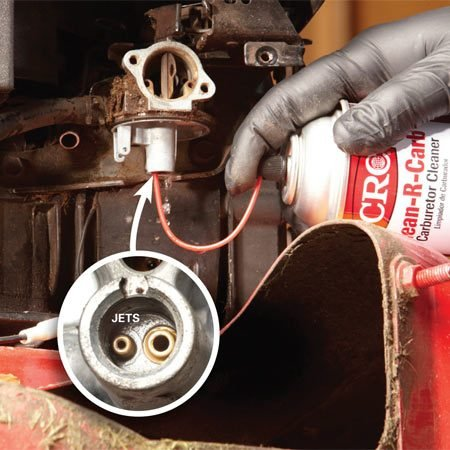 <b>Photo 5: Clean the main jet</b></br> Remove the carburetor bowl nut. Insert the carburetor cleaner straw directly into the main jet passage and squeeze the trigger on the can several times until the spray shoots into the venturi of the carburetor. That'll confirm the passage is open.