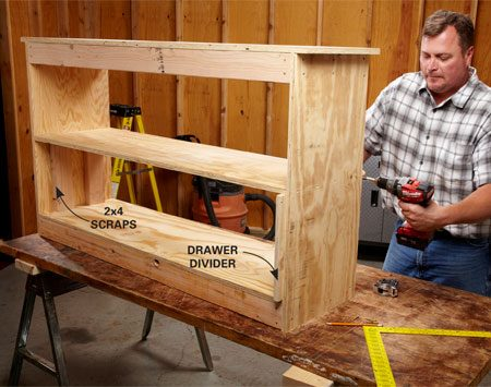 <b>Photo 2: Add a shelf</b></br> Temporarily support the shelf using the drawer divider and a couple of 2x4 scraps. To avoid splitting the plywood shelf, predrill holes through the sides and into the shelf before fastening with screws.