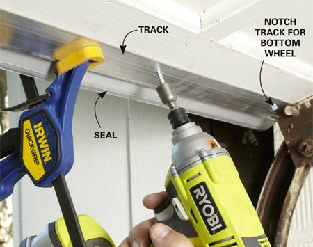 <b>Photo 4: Fasten a new bottom seal to a wood garage door</b></br> Push the track into wet caulk and tight against the door bottom. Clamp it into place. Then drill and screw the track to the back of the door using 1-in. screws.