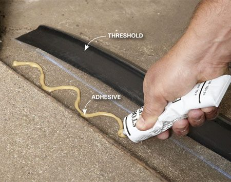 <b>Photo 6: Glue down a new threshold</b></br> Squirt out a bead of threshold adhesive according to label directions. Then move the threshold into place and align it with the chalk line you made earlier. Close the garage door and let the weight hold it in position until the adhesive sets up.