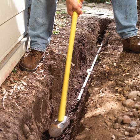 <b>Running cable</b></br> Drive conduit under concrete with a sledge, uncap the ends and run the cable.