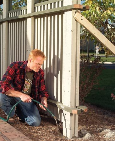 <b>Moisten dry concrete</b></br> Pour dry concrete mix around a post and moisten it after assembling the fence.