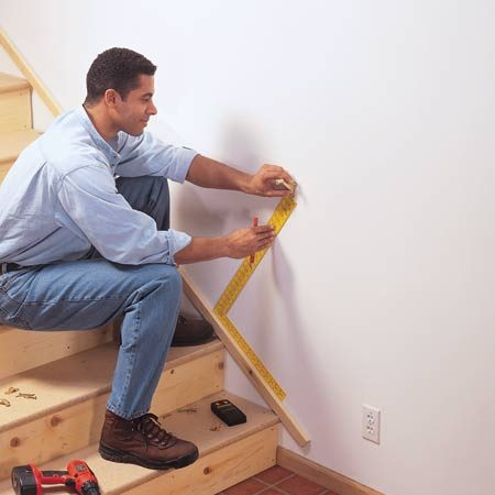 <b>Position a stair rail</b></br> Use a board and framing square to establish anchor points for a handrail.