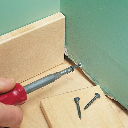 <b>Shim baseboard</b><br/>Turn a screw in or out to support and flatten baseboard against drywall.