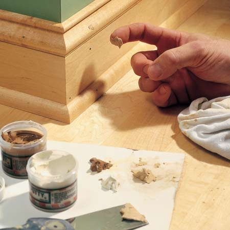 <b>Fill nail holes</b></br> Mix several shades of putty to exactly match the wood color around the nail hole.