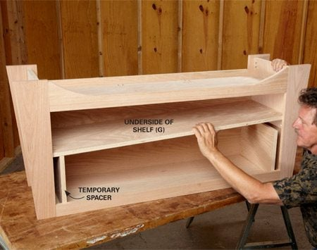 <b>Photo 7: Install the shelf</b><br/><p>With the stand upside down, set the shelf on 9-1/2-in. temporary spacers and screw it into place. Then install the dividers below the shelf.</p>