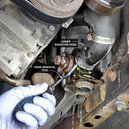 <b>Photo 1: Remove the lower hose</b></br> Slip the pointed end of the removal tool all the way into the end of the hose. Then pull it around the radiator neck to break the hose loose. Pull it off quickly and immediately direct the coolant into the drain pan.