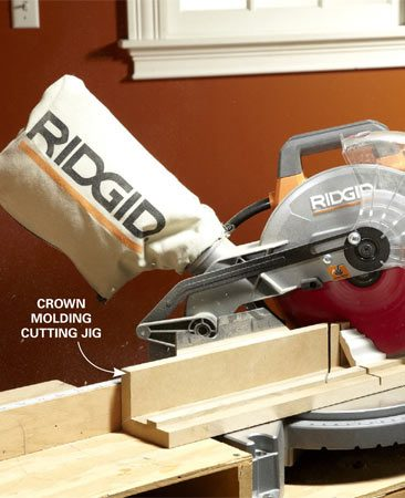 <b>Photo 6: Build a crown molding jig</b></br> Build a simple jig to hold the crown molding at the correct angle while you cut it (see below). Position the molding upside down and set the saw to 45 degrees. Avoid cutting all the way through the jig.