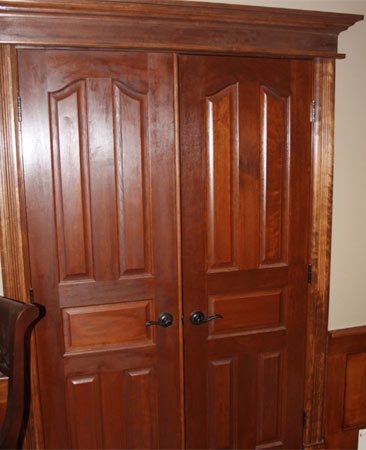 <b>Solid cherry door trim</b></br> For the crowning touch, Matt installed solid cherry doors, and then trimmed them in this traditional style with poplar stained to match.