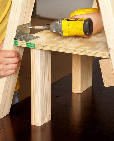 <b>Attaching the shelf</b></br> Cut two blocks of wood to temporarily hold the shelf in place while you fasten the hinged side of the shelf to the legs.