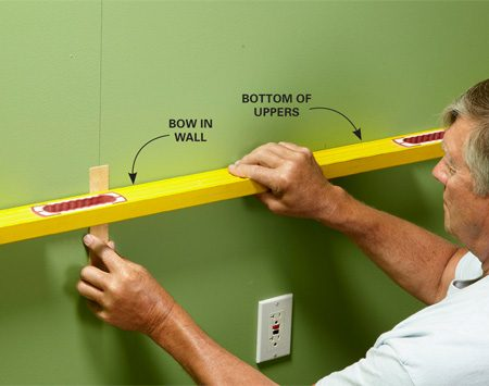<b>Check wall for problems</b><br/>Most of the time you can shim the cabinets as you go, but if there's an extreme bow in the wall (more than 3/8 in.), shim it out before you hang the cabinet. If you don't, you may accidentally pull the back off the cabinet while fastening it into place. Hold a level across the wall, and slide a shim up from the bottom (go in from the top when you're doing the top side) until it's snug. Then pin or tape it into place.