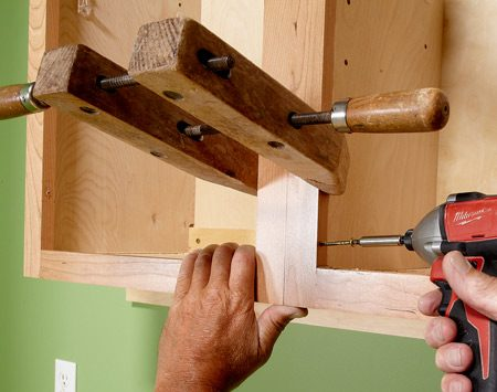 <b>Join face frames</b><br/>When connecting two cabinets to each other, line up the face frames and clamp them together. Both cabinets should be fastened to the wall at this point, but you may have to loosen one cabinet or the other to get the frames to line up perfectly. Jerome prefers hand-screw clamps because they don't flex, and less flex means a tighter grip. Predrill a 1/8-in. hole before screwing them together with a 2-1/2-in. screw. Choose the less noticeable cabinet of the two for drilling and placing the screw head.