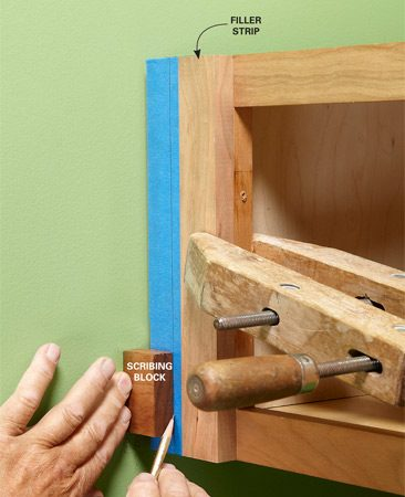 <b>Scribing trick</b><br/>Find the largest distance between the outside of the cabinet and the wall. Take that measurement and make a pencil mark on your filler strip (measure over right to left in this case). Clamp the filler onto the cabinet flush with the inside of the vertical rail. Measure over from the wall to your pencil mark, and make a scribing block that size. Use your block to trace a pencil line down the filler strip. Masking tape on the filler strip helps the pencil line show up better and protects the finish from the saw table.