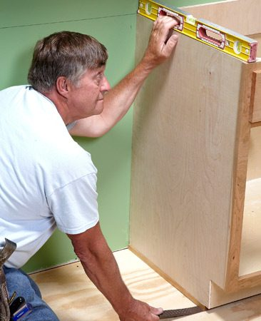 <b>Level the sides</b><br/>Line up the base cabinets with the level line on the wall. Fasten the back of the cabinets to that line. Once the backs of the cabinets are level, use shims to level the sides. Take your time on this step&mdash;nobody likes to have eggs roll off a slanted countertop.
