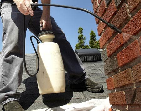 <b>Photo 3: Spray the brick with water repellent</b></br> Start at the bottom of the chimney and spray the brick until the excess repellent runs down about 8 in. below the spray line. Work your way up to the top. Apply a second coat within five minutes using the same technique.
