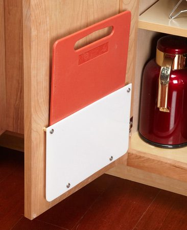 <b>Cabinet organization tip</b><br/><p>The slickest way to store a  cutting board for   instant access is shown in the  next tip. But that only   works for cutting boards less  than 10-1/2 in. wide.   For larger boards, mount a  rack on a cabinet door.   I used a sheet of  1/4-in.-thick acrylic plastic, but   plywood would also work. You  can cut acrylic   with a table saw or circular  saw as long as you cut   slowly. Knock off the sharp  edges with sandpaper.   I also rounded the lower  corners with a belt   sander. For spacers, I used  No. 14-8 crimp sleeves   (in the electrical aisle at  home centers). But any type of tube or even blocks of wood would work.</p>