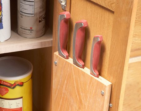<b>Cabinet door storage</b></br> <p>You can size this knife rack  to   suit any cabinet door and any   number of knives. To build it,   you just need a table saw and   wood scraps. Run the scraps   across the saw on edge to cut   kerfs. Adjust the blade height   to suit the width of the knife   blades. You have to remove   the saw's blade guard for   these cuts, so be extra  careful.   Also cut a thin strip to act   as an end cap. Glue and   clamp the kerfed scraps   together and sand the knife   rack until the joints are  flush.   To mount it, use two 1-1/4-in. screws and finish washers.</p>