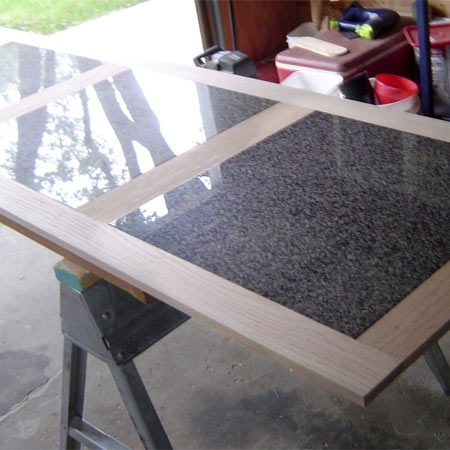 <b>Assembling the top</b><br/>Inset tightly in an oak frame and then laid on a plywood base, these oversize granite tiles make a perfect bar top.<br/>Reader Photo