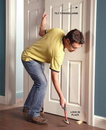 <b>Photo 1: Square the door</b></br> Push the door against the jamb and lock it in place with shims at both corners.