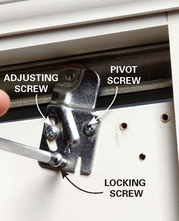 <b>Photo 2: Tighten screws</b></br> Remount in new screw holes if necessary. Then test the door to make sure it rolls smoothly.