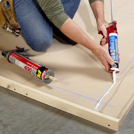 <b>Photo 2: Start with the bottom rail</b></br> Run beads of construction adhesive and caulk before nailing on the rails and stiles. The caulk locks out moisture along the edges while the adhesive provides long-term holding power.