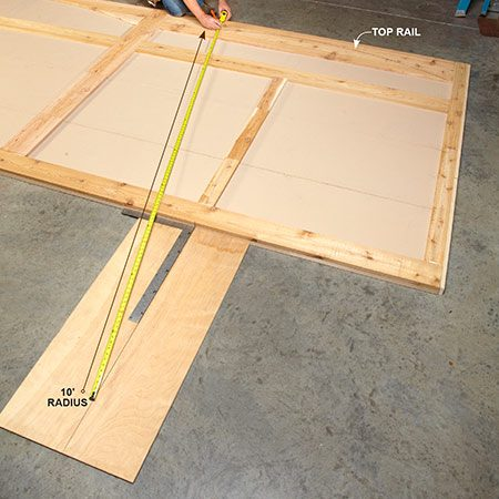 "<b>Photo 4: Mark arches on the top rails</b></br> Center a scrap of plywood below the door and drive in a screw to act as a pivot point. Hook on your tape measure, hold your pencil at the desired radius and ""swing"" an arch across the top rail. In this case, the 10-ft. mark on the tape provided the perfect radius. Cut the arch with a jigsaw."