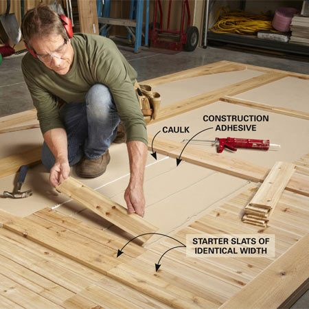 <b>Photo 7: Install the slats</b></br> Run triple beads of construction adhesive and a single bead of silicone caulk at the top of the door panel, then nail the slats into place, one by one.
