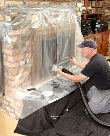 <b>Photo 3: Protect your interior</b><br/>Lay a canvas tarp over the hearth and spread it into the room. Then tape poly sheeting over the fireplace and insert a shop vacuum hose. Seal everything with duct tape.