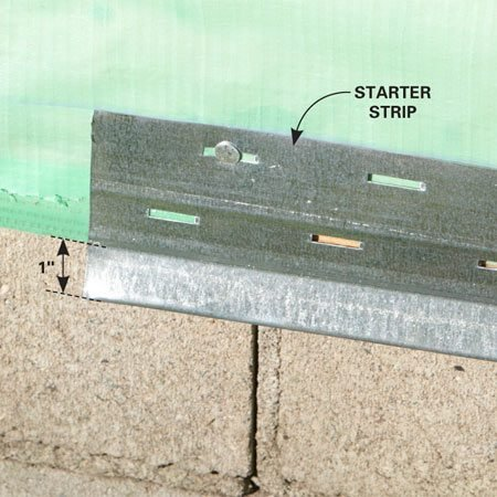 <b>Keep bugs and moisture out</b></br> The bottom of the starter strip (the part the bottom panel hooks on to) should be at least 1 in. below the top of the foundation, but the lower the siding is installed, the better. It protects the sheathing from rain, snow and pests. Most suppliers sell two sizes of starter, 2-1/2 in. and 3-1/2 in. Spend the extra few bucks on the wider stuff and start your siding a bit lower.